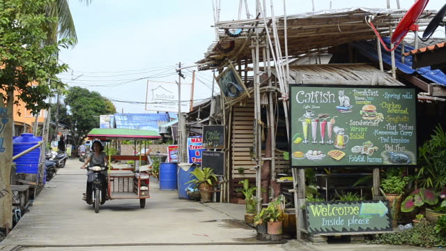ms shot of motorbike taxi driving past restaurant menu sign in ban saladan / island ko lanta, krabi province, thailand - ko lanta stock videos & royalty-free footage
