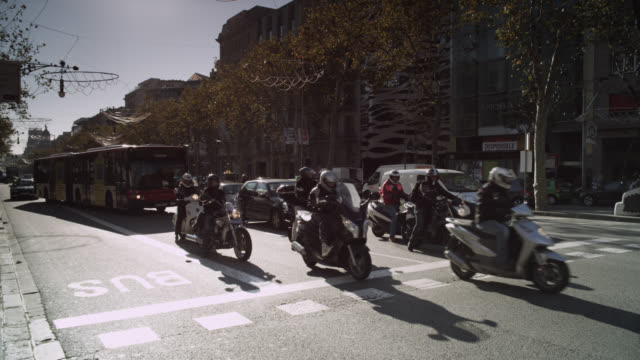 MS PAN Shot of Motorcycles and cars starting on street, men crossing / Barcelona, Catalunya, Spain