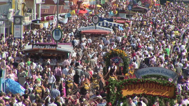 MS shot of moving horse waggon carrying beer through crowd, street on Oktoberfest / Munich, Bavaria, Germany