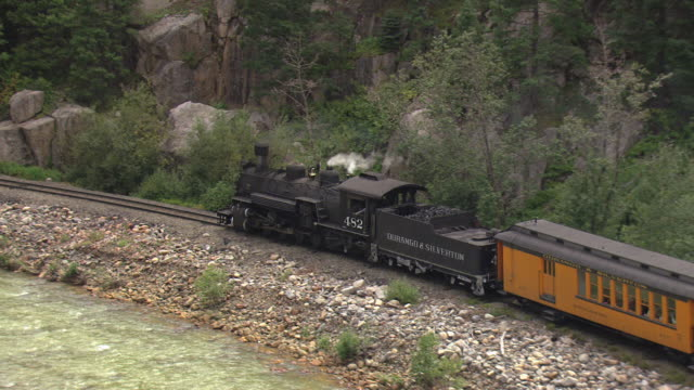 ms ts zo aerial shot of moving steam train on tracks from near river / telluride, colorado, united states - steam train stock videos & royalty-free footage