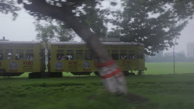 ms pov ts shot of moving tram train through trees / kolkata, west bengal, india - victoria memorial kolkata stock videos and b-roll footage