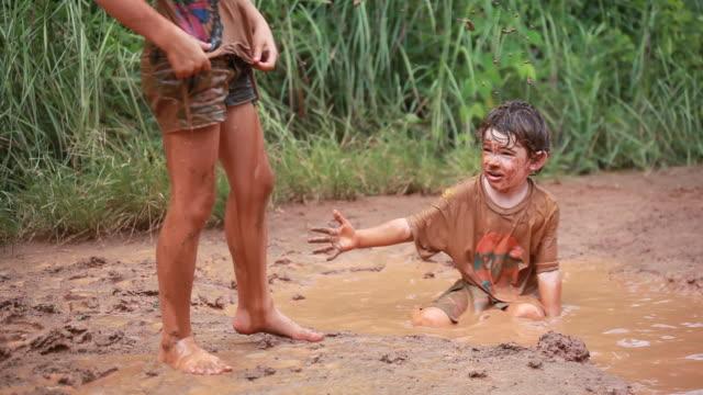 MS Shot of muddy little boy in mud puddle throws mud packs at little muddy girl / Montezuma, Punteranes, Costa Rica