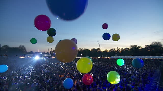 MS POV Shot of Multi-colour balloons in air looking down on festival crowd hitting them up into air / Victoria Park, London, United Kingdom