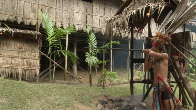 vidéos et rushes de ms shot of murut man using traditional blow pipe / kota kinabalu, sabah, malaysia   - malaysian culture