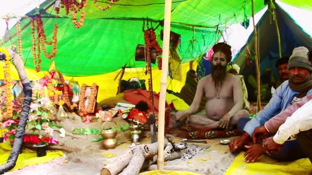 ms pan shot of naga sadhu with pilgrims in tent in kumbh mela / allahabad, uttar pradesh, india - 真鋳点の映像素材/bロール