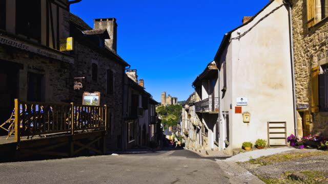 ms t/l tu shot of najac empty street with restaurant and old houses with royal castle / najac, midi-pyrenees, france - wide shot stock videos & royalty-free footage