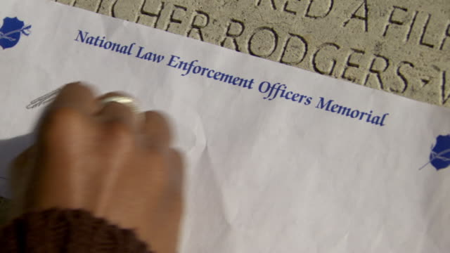 ECU TD Shot of names carve in stone at National Law Enforcement Officers Memorial and person etching Lucille C Ross name on piece of paper / Washington, District of Columbia, United States