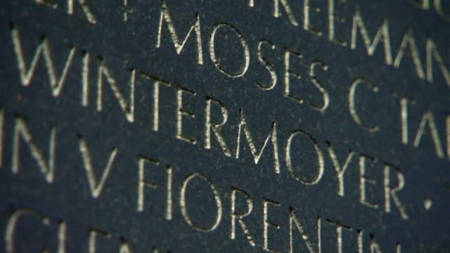 ecu td shot of names engraved on vietnam veterans memorial wall / washington, district of columbia, united states - vietnam veterans memorial video stock e b–roll