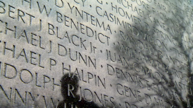 ms shot of names engraved on vietnam veterans memorial wall with reflections of people walking alongside wall / washington, district of columbia, united states - vietnam veterans memorial video stock e b–roll