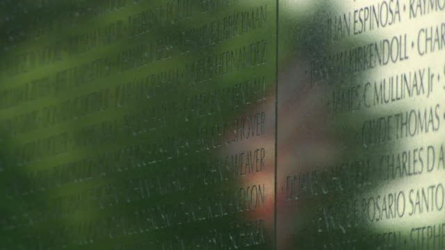 stockvideo's en b-roll-footage met cu r/f shot of names engraved on vietnam veterans memorial wall with reflection of american flag / washington, district of columbia, united states - vietnam veterans memorial