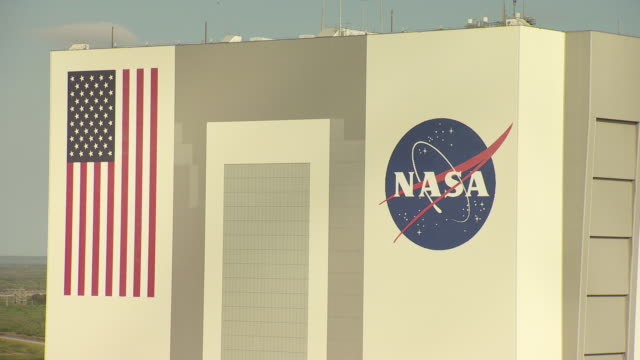 CU AERIAL Shot of NASA signage and American Flag on Vehicle Assembly Building at Kennedy Space Center / Florida, United States
