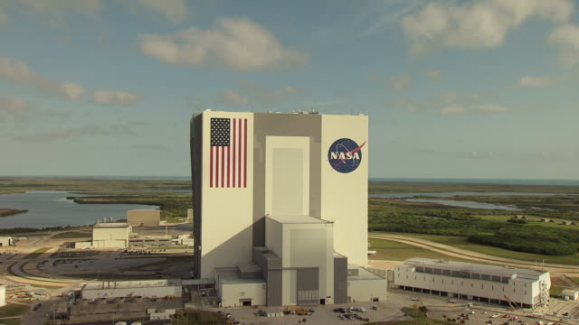 MS AERIAL ZO Shot of NASA signage and American Flag on Vehicle Assembly Building with parking lot and other buildings at Kennedy Space Center / Florida, United States / Florida, United States