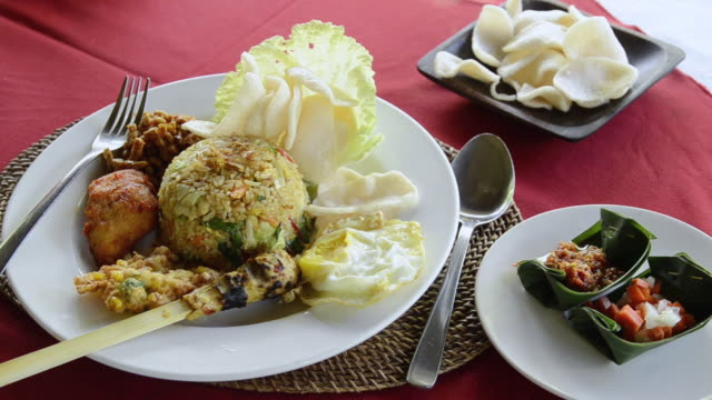 cu shot of nasi goren dish in fried rice with chicken, egg, kerupuk crackers and balinese food  / ubud, bali, indonesia - 飲食点の映像素材/bロール