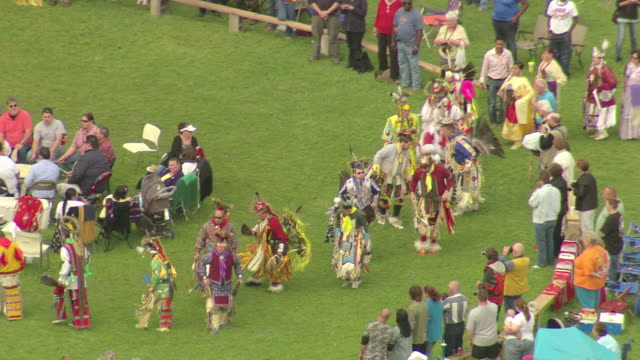 ms aerial shot of natchez powwow native american celebration with flag procession and people watching native americans dressed in traditional clothes dancing / mississippi, united states - nordamerikansk indiankultur bildbanksvideor och videomaterial från bakom kulisserna