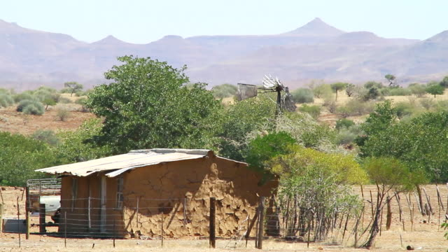 ms shot of native structure with mountainous and tree / darmaland, kunene, namibia - wiese stock videos & royalty-free footage