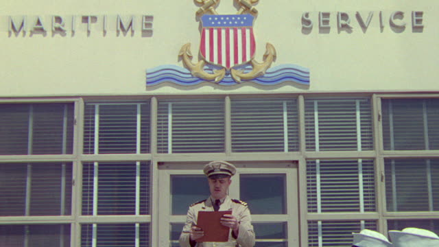 stockvideo's en b-roll-footage met ms zo shot of navy officer reading list outside training centre with number of cadets - amerikaanse zeemacht