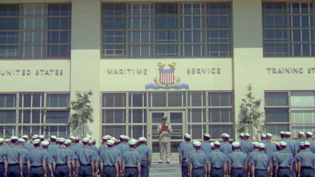 ws shot of navy officer reading list outside training centre with number of cadets - us navy stock videos & royalty-free footage