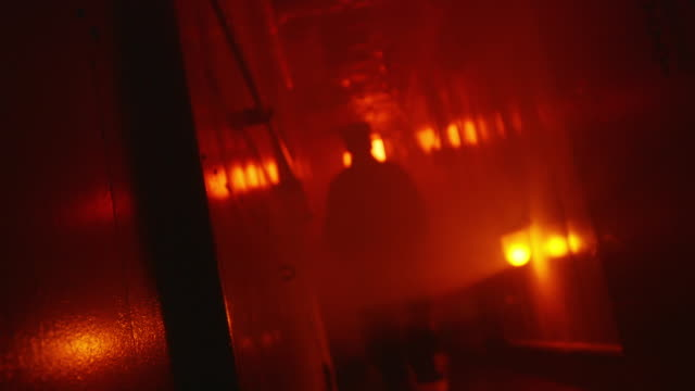 cu la shot of navy sailors inside lst run along tight corridor under red emergency light / evansville, indiana, united states - militärschiff stock-videos und b-roll-filmmaterial