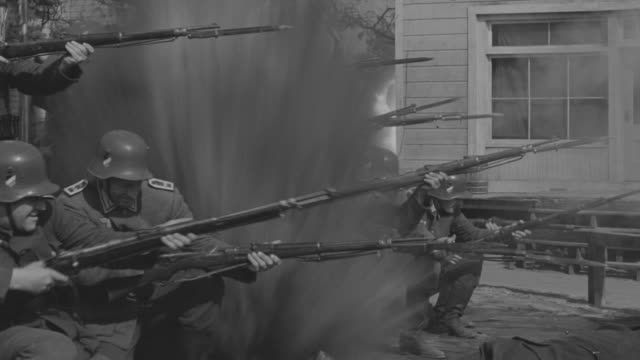 stockvideo's en b-roll-footage met ms shot of nazi soldiers firing on town people battle with explosion - nazisme