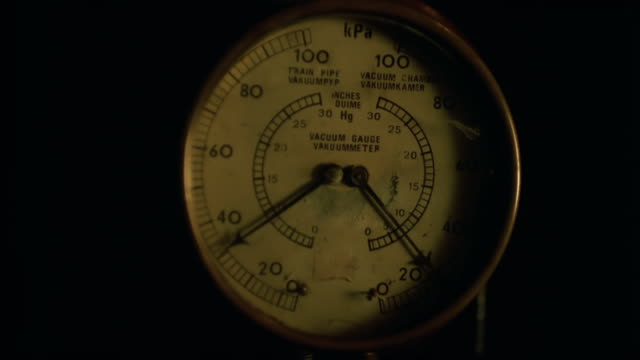 CU T/L shot of needles of vacuum gauge moving then hand wiping instrument / South Africa