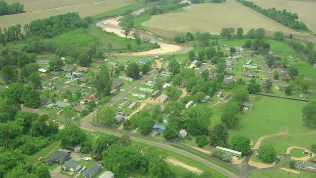 MS AERIAL ZO Shot of neighborhood with river and farmland / Charleston, Mississippi, United States