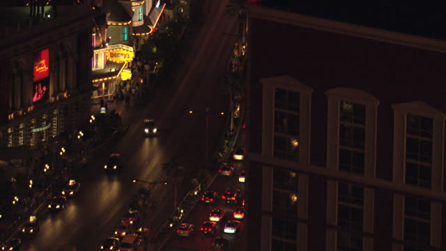 MS AERIAL Shot of neon signs at night on Strip at Mirage and Ceasars Palace and Treasure Island above traffic in street / Las Vegas, Nevada, United States