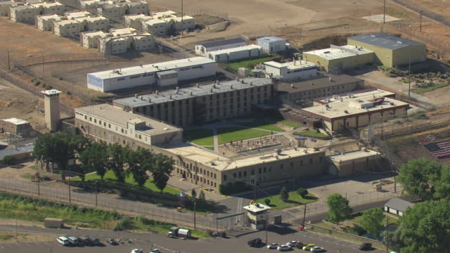 ms aerial shot of nevada state prison campus and buildings and surrounding barbed wire fence / carson city, nevada, united states - prison building stock videos & royalty-free footage