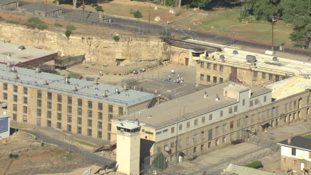 ms aerial shot of nevada state prison campus and prisoners playing basketball on outside court on a sunny day / carson city, nevada, united states - prison building stock videos & royalty-free footage