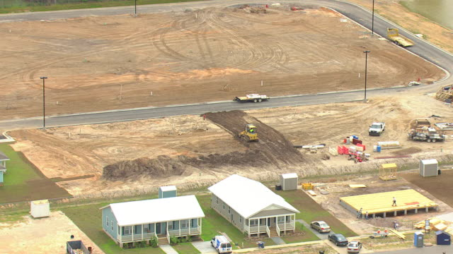 vídeos y material grabado en eventos de stock de ms aerial zi shot of new houses in pastel colors and bulldozer pushing dirt on empty lot / waveland, mississippi, united states - terrenos a construir