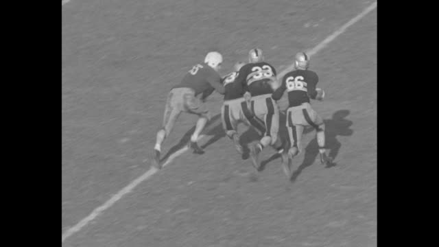 """shot of newspaper headline, """"army and notre dame win, 14-8, 14-0"""" / yale and army teams run on field, one player tackles another / new play and... - アメフト ファーストダウン点の映像素材/bロール"""