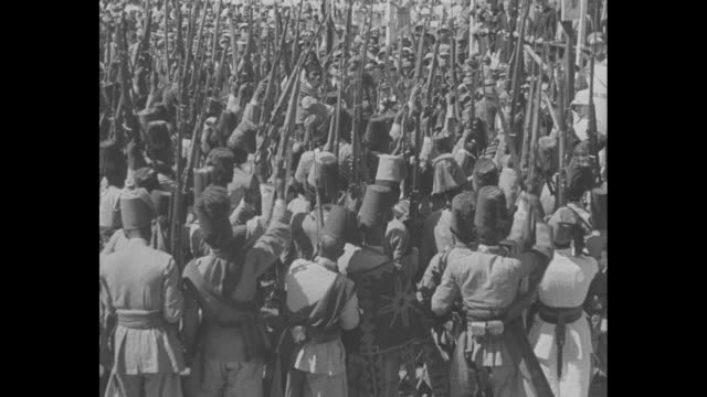 "stockvideo's en b-roll-footage met shot of newspaper headline, ""italy starts 2-front push on 'rome day'"" / african dancers in native costume play drums and jump / dancers and marchers... - 1930"