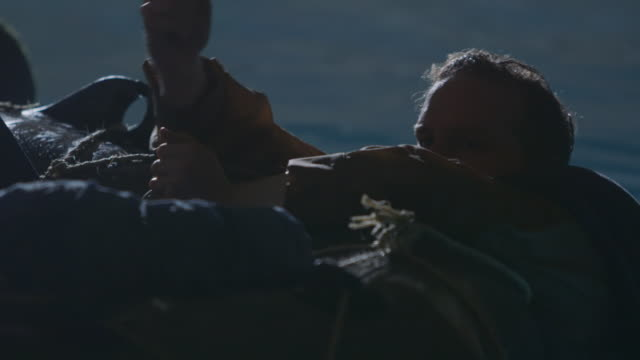 cu pan shot of night scene soldier tries to hang on to life raft after his ship is attacked during world war ii / southampton, united kingdom - 溺れる点の映像素材/bロール
