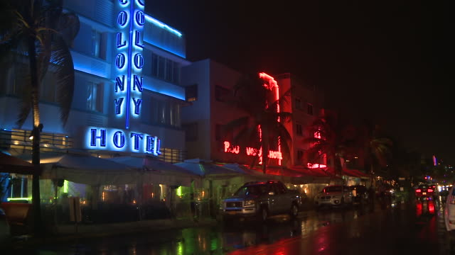 ms shot of night traffic on rainy night on ocean drive with hotels / miami beach, florida, united states - アールデコ地区点の映像素材/bロール