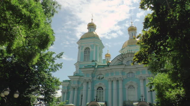 ms shot of nikolsky cathedral against blue sky and scattered clouds / st. petersburg, russia - 四匹点の映像素材/bロール