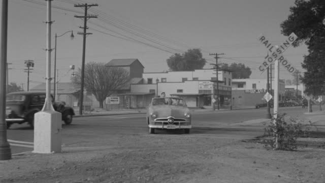 MS TS PAN Shot of nondescript street in small town at intersection of railroad crossing, Car drive on street