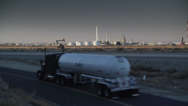 ws shot of north coles levee fractionator gas plant and tupman road with a energy natural gas container truck passing / taft, california, united states - gas stock videos & royalty-free footage