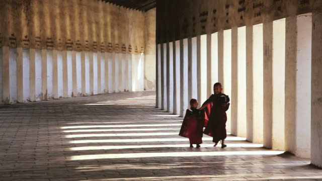 WS Shot of Novice Monks dressed in traditional clothes in Walkway to Shwezigon Pagoda / Bagan, Burma