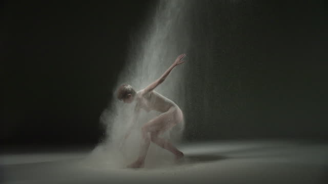 WS SLO MO Shot of nude female Caucasian, gets up and spins around powder is thrown at her / Studio, New York, United States
