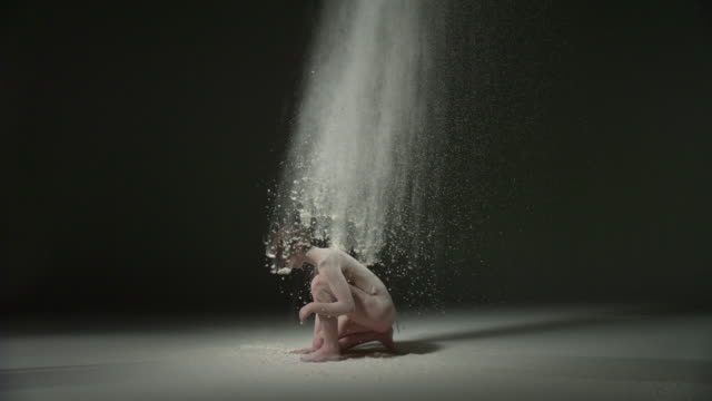 ws slo mo shot of nude female caucasian, gets up and spins around powder is thrown at her / studio, new york, united states - naturist stock videos & royalty-free footage