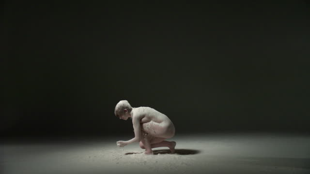 ws slo mo shot of nude female caucasian, gets up and spins around powder is thrown at her / studio, new york, united states - langsam stock-videos und b-roll-filmmaterial