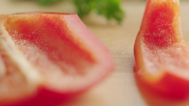 ecu r /f shot of of organic red bell pepper on kitchen cutting board, one strip is cut from larger section of pepper with steel knife / los angeles, california united states - peperone video stock e b–roll