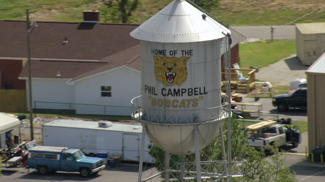 vídeos de stock, filmes e b-roll de cu aerial shot of of tall water tank with home of phil campbell bobcats sign / phil campbell, alabama, united states - localidade pequena