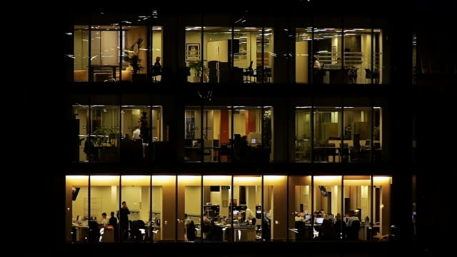 MS T/L Shot of Office building showing workers lit up inside at night / London, United Kingdom