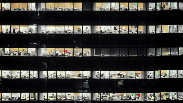 ms t/l shot of office workers working late in multi story building in shiodome / tokyo, japan - kontorsbyggnad bildbanksvideor och videomaterial från bakom kulisserna