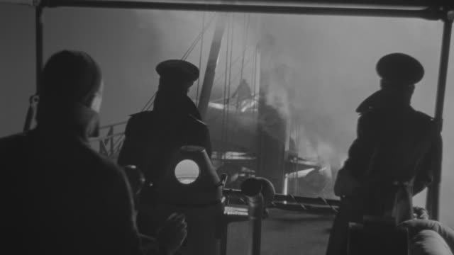 ms shot of officer watching from military ships through fog - 舵輪点の映像素材/bロール