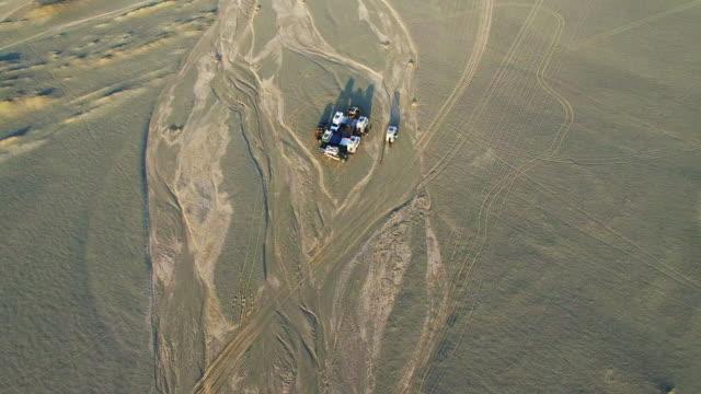 ws aerial shot of off-road vehicles camping in gobi at sunset./xinjiang,china. - 新疆ウイグル自治区点の映像素材/bロール