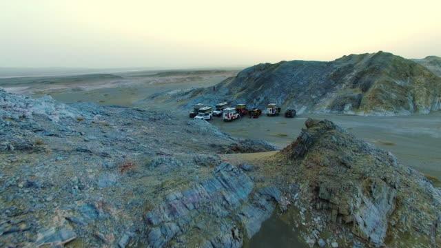 ws aerial shot of off-road vehicles camping in ravine at sunset/xinjiang,china. - 新疆ウイグル自治区点の映像素材/bロール
