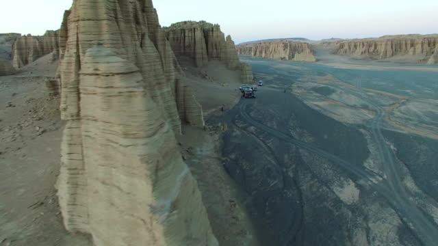 ws aerial shot of off-road vehicles camping in yardang landform at sunset,xinajing,china. - 新疆ウイグル自治区点の映像素材/bロール