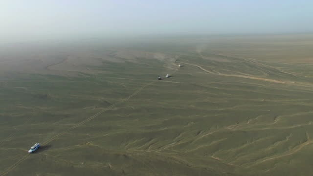 WS AERIAL shot of off-road vehicles driving in Gobi./Xinjiang,China.