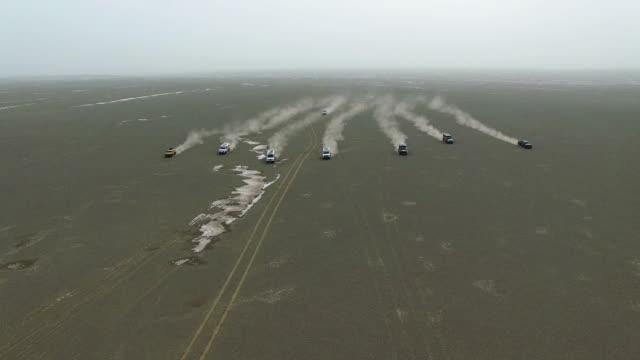 ws aerial shot of off-road vehicles driving in gobi./xinjiang,china. - traccia video stock e b–roll